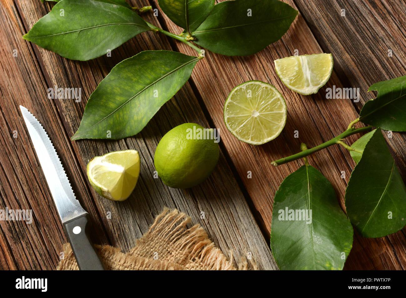 Lime frutti con foglie su un tavolo di legno - Frutta tropicali con proprietà antiossidanti - primo piano Immagini Stock
