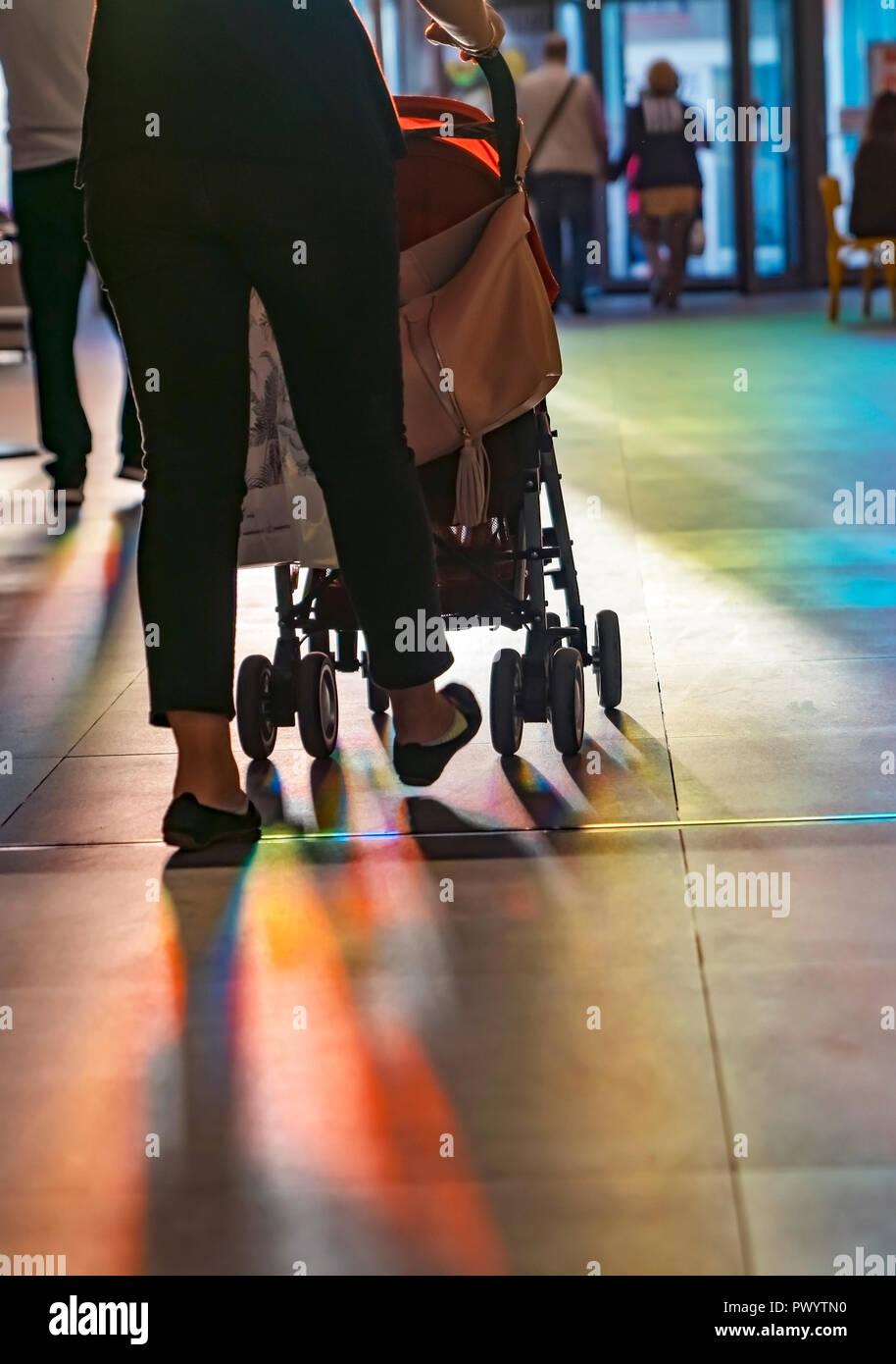 Giovane madre a piedi con bambino trasporto nel centro dello shopping, dal retro, serata di sole raggiungere al suo interno attraverso una porta a battente. Foto Stock
