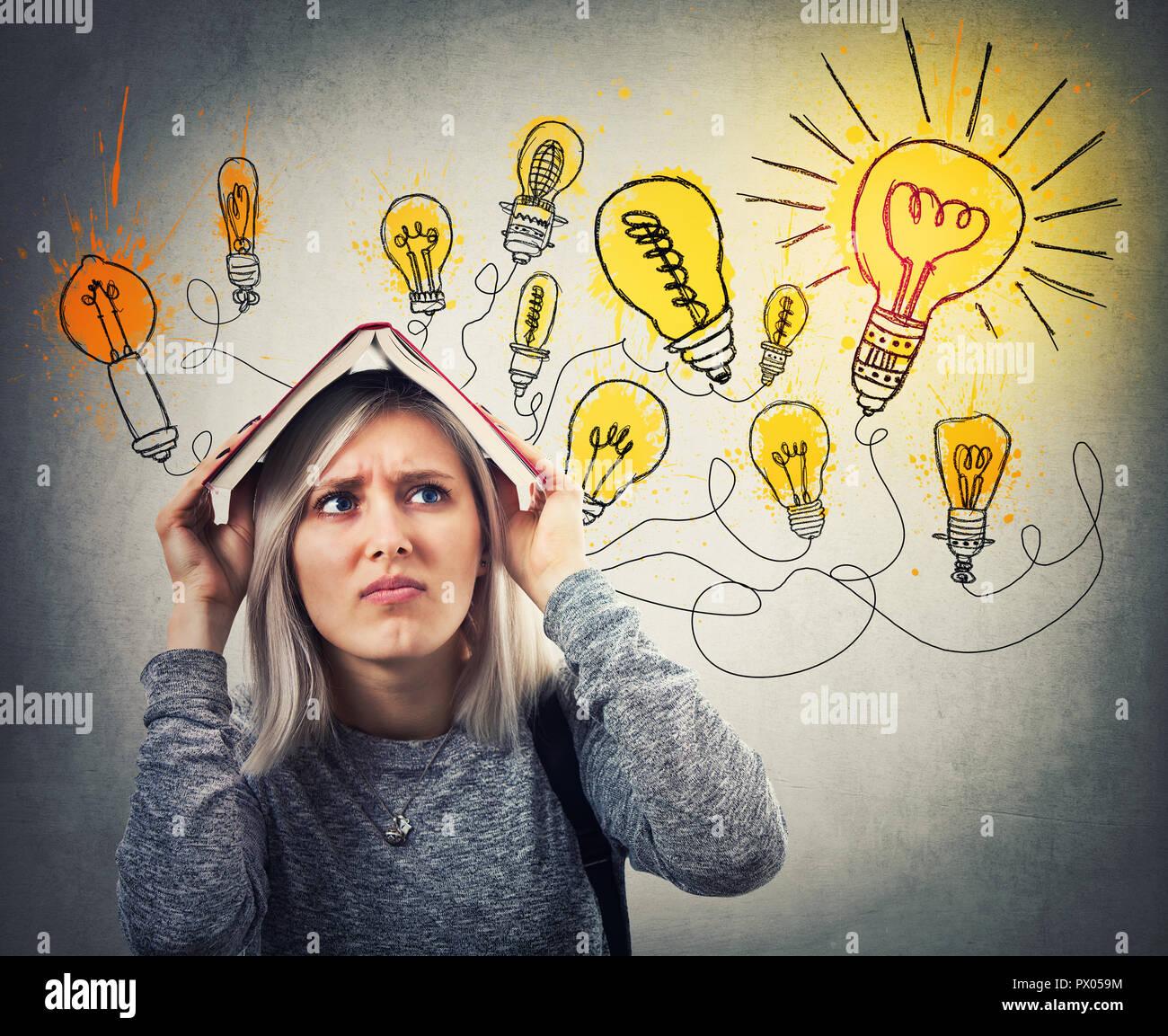 Perplesso giovane donna in possesso di un libro aperto sopra la testa avente molte idee, ha per scegliere la migliore. Ha sottolineato l'emozione, duro pensare guardando shining li Immagini Stock