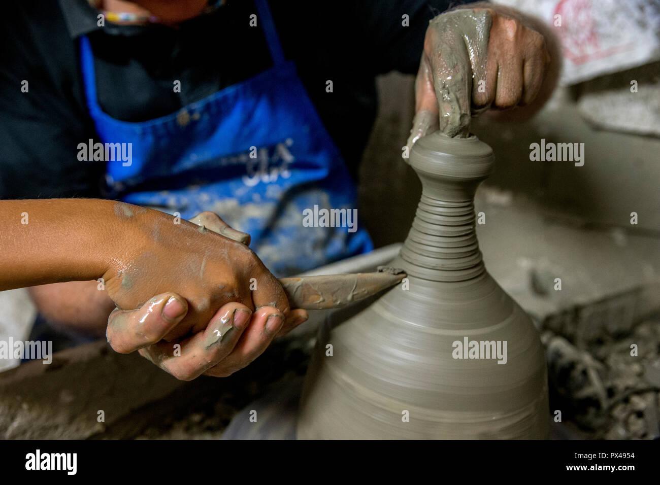 Laboratorio di ceramica a Tricase, Puglia, Italia. Adulto che mostra un bambino la ceramica tecnica. Immagini Stock
