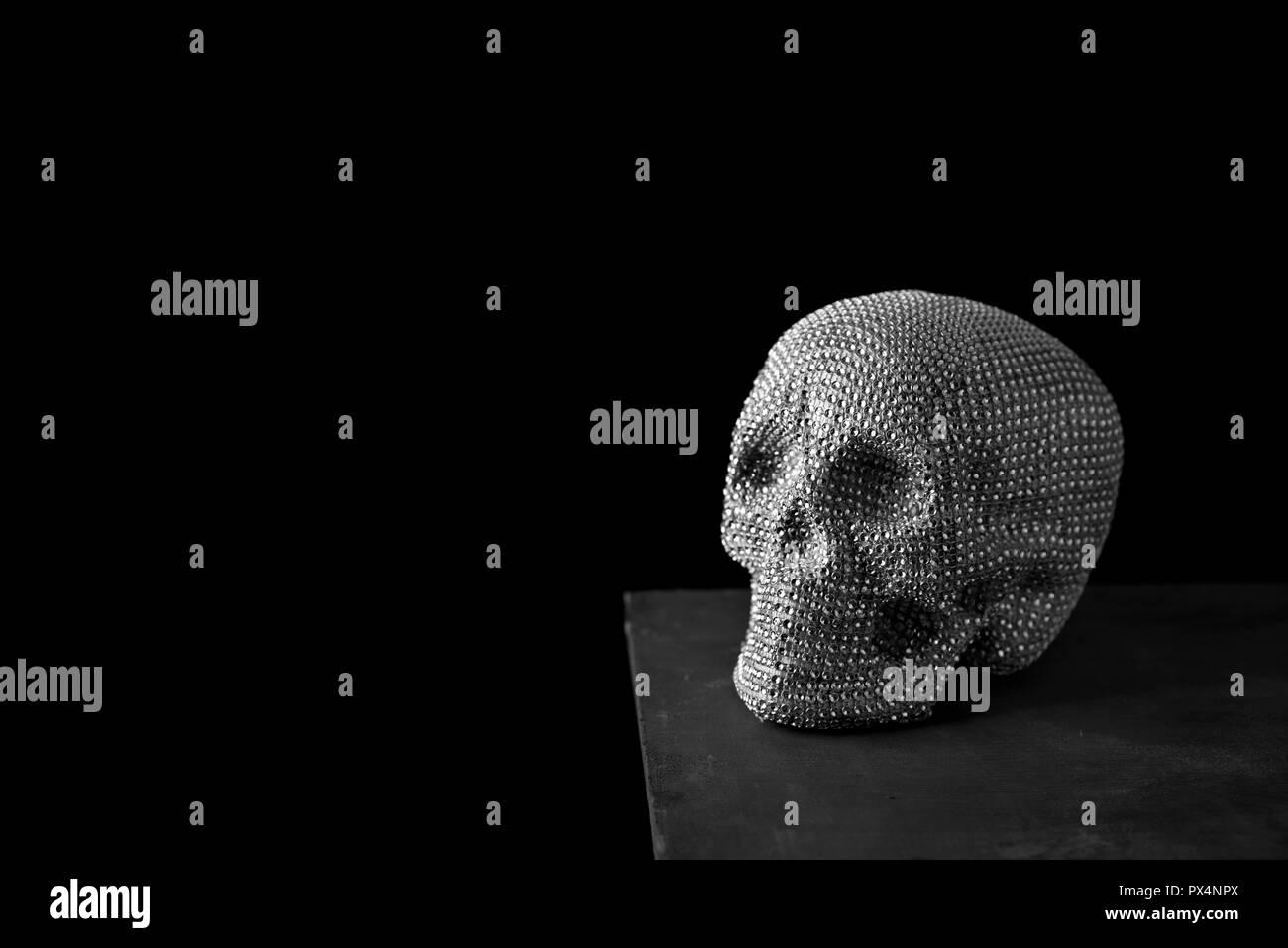 Primo piano di un cranio scintillanti su un grigio scuro superficie contro uno sfondo nero con un po' di spazio vuoto sulla sinistra Immagini Stock