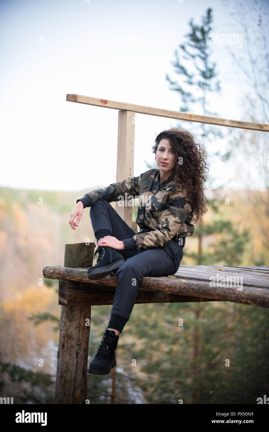 La donna siede su l'altitudine durante una escursione Immagini Stock