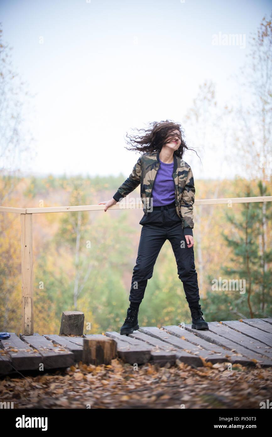 Curly donna fruste i suoi capelli all'altitudine durante una escursione Immagini Stock