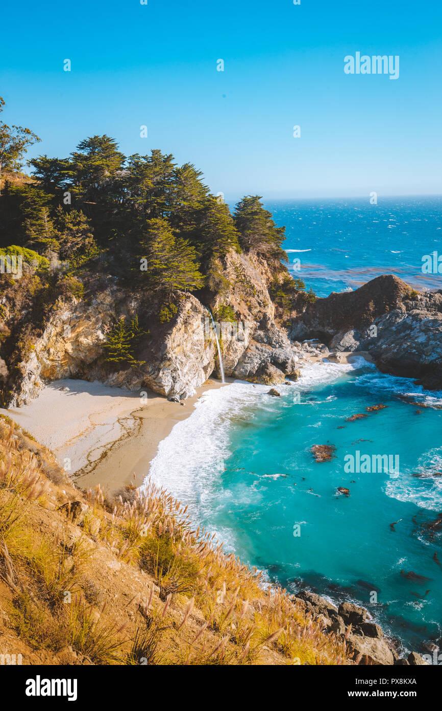 Classic vista da cartolina famosa McWay cade in scenic golden luce della sera al tramonto di una bella giornata di sole con cielo blu in estate, CALIFORNIA, STATI UNITI D'AMERICA Immagini Stock