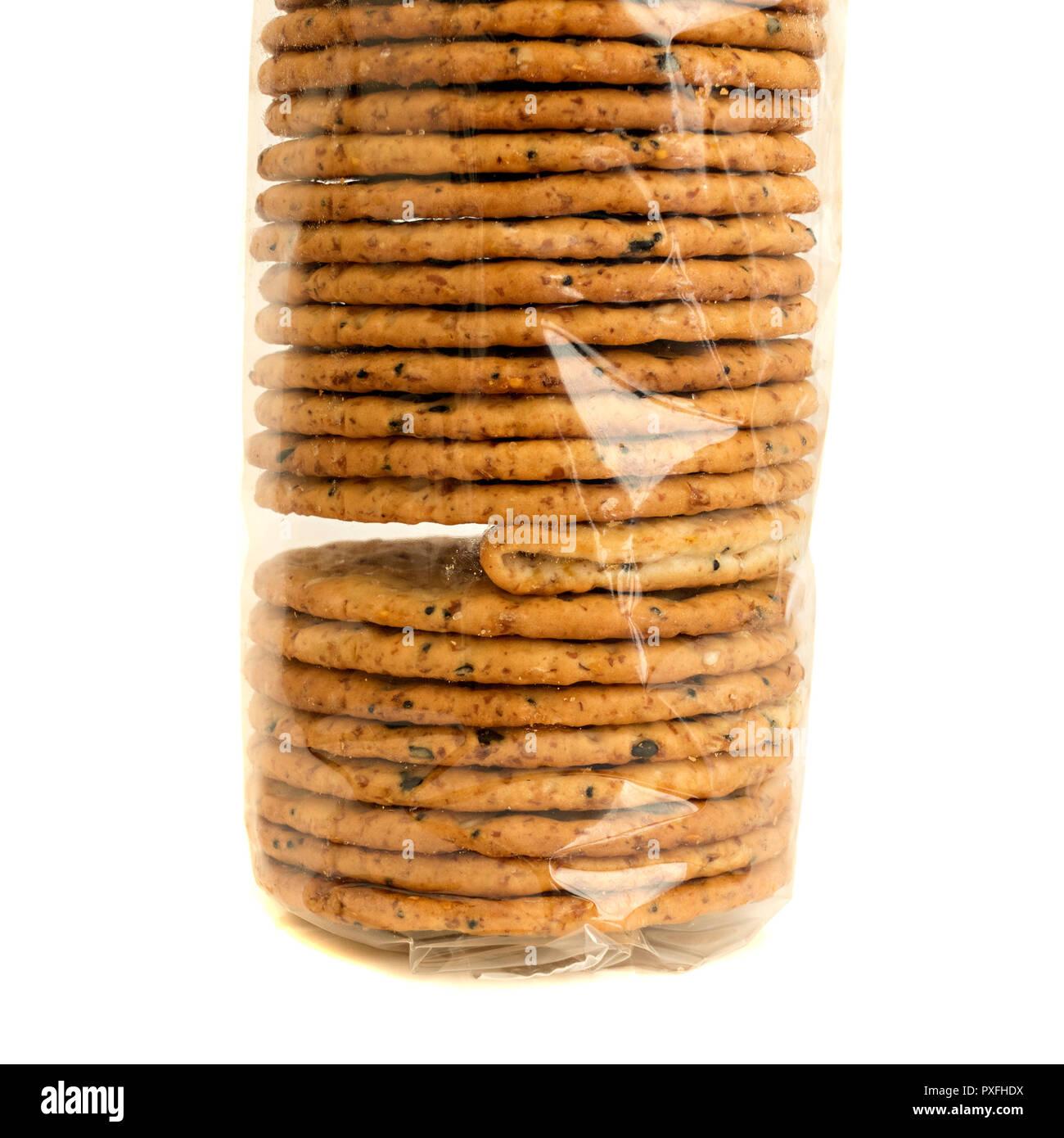 """""""L'intruso"""" un pacchetto di cellophane trasparente avvolto biscotti con uno difettoso cracker ripiegata che illustra un problema o un guasto nel controllo di qualità. Immagini Stock"""