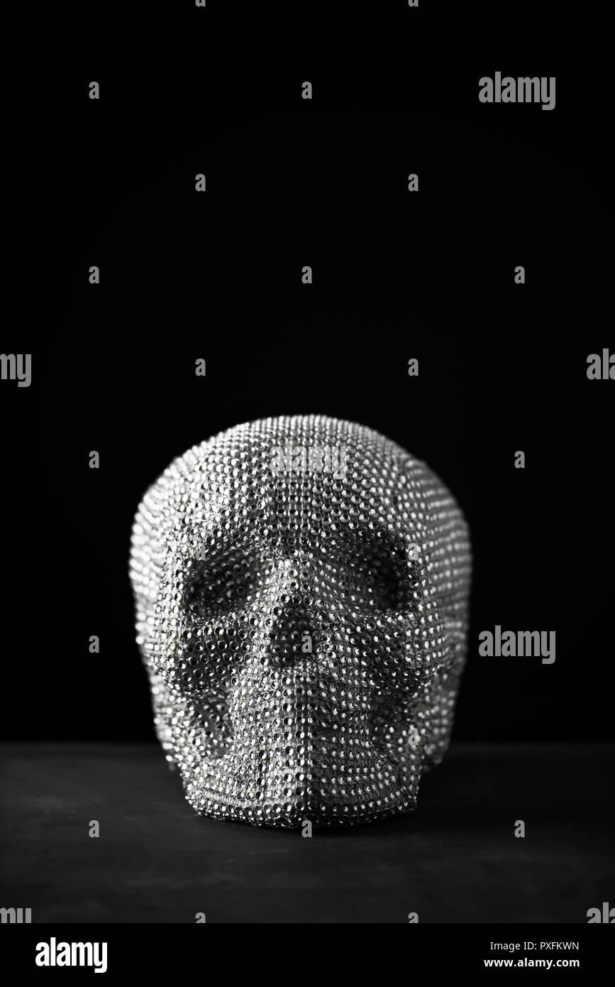 Primo piano di un cranio scintillanti su un grigio scuro superficie contro uno sfondo nero con un po' di spazio vuoto sulla parte superiore Immagini Stock