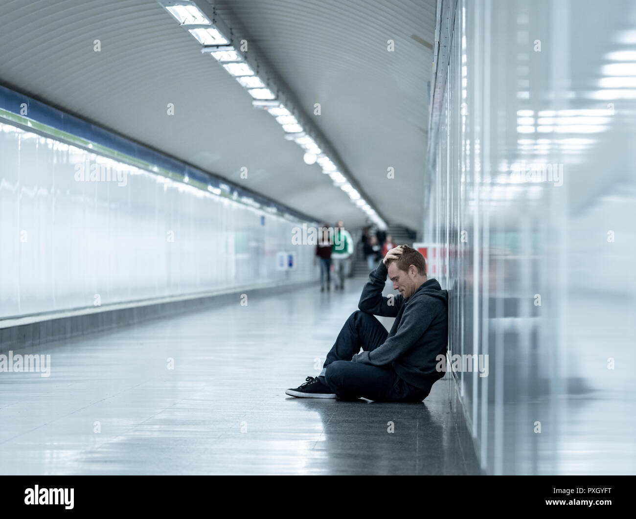 Misere disoccupato giovane uomo grida tossicodipendente senzatetto in depressione stress seduta sul terreno street subway tunnel alla ricerca disperata appoggiata sulla parete Immagini Stock