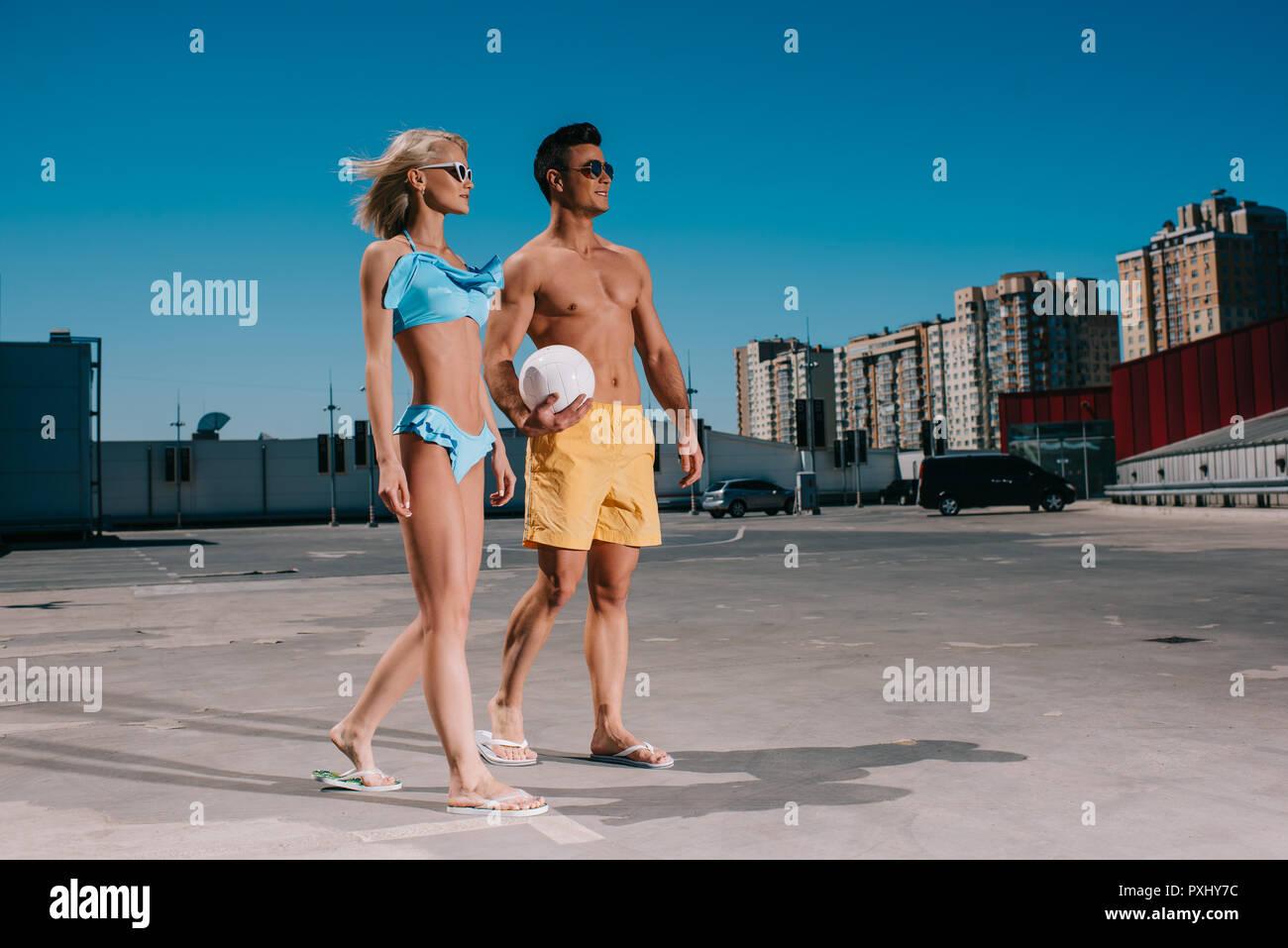 Coppia giovane in vestiti in spiaggia con sfera di pallavolo su parcheggio Immagini Stock
