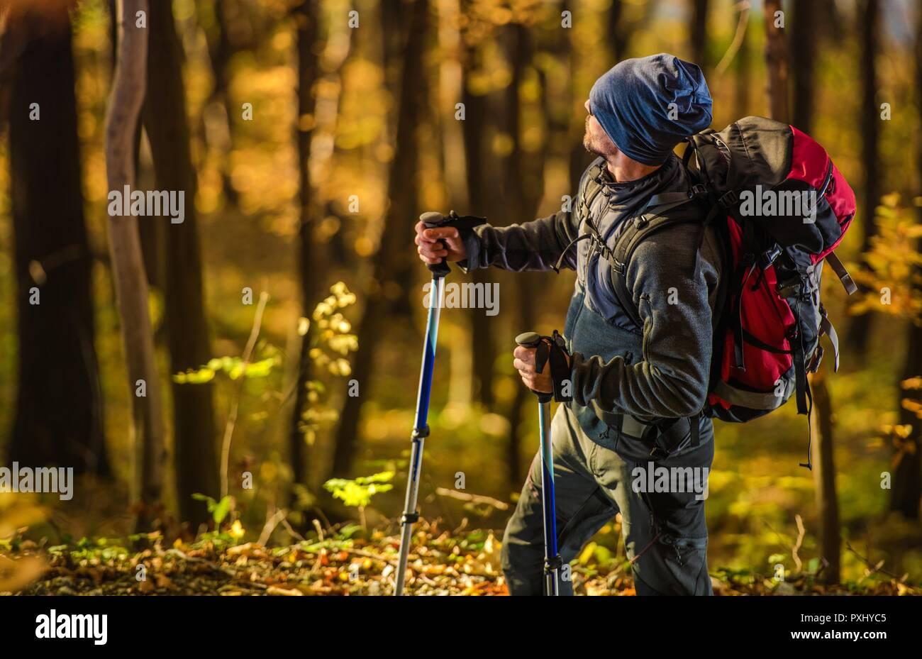 Escursionista caucasica nel bosco durante la Scenic Golden caduta delle foglie. Gli uomini con zaino sul sentiero. Immagini Stock