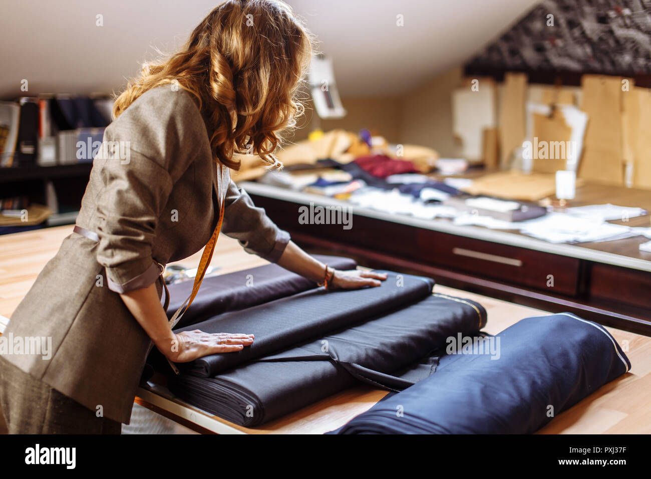 Moda femminile designer che lavora su tessuto si adattano con accessori di sartoria su tavola Immagini Stock