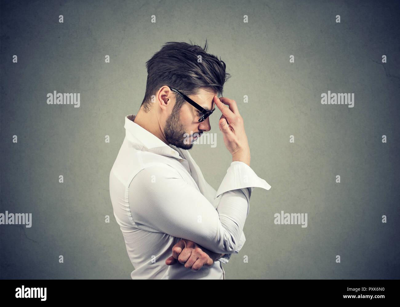 Vista laterale di uomo barbuto in bicchieri e camicia bianca toccando la fronte essendo in depressione e piena di pensieri Immagini Stock
