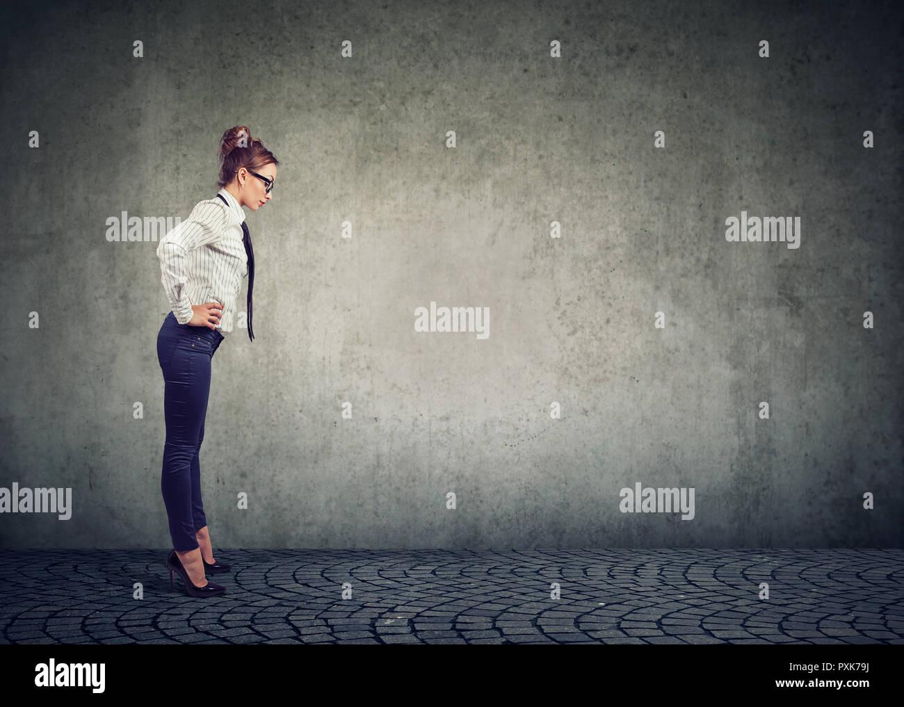 Vista laterale della donna formale sui tacchi alti guardando giù nella confusione essendo curioso contro uno sfondo grigio Immagini Stock