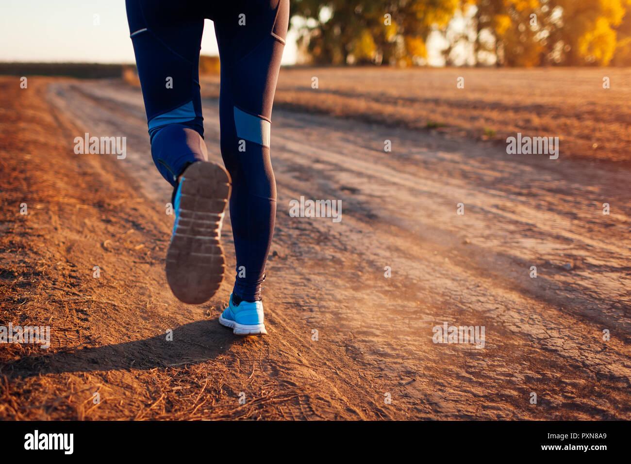 La donna in esecuzione nel campo di autunno al tramonto. Uno stile di vita sano concetto. Attiva le persone sportive. Close up di gambe Foto Stock