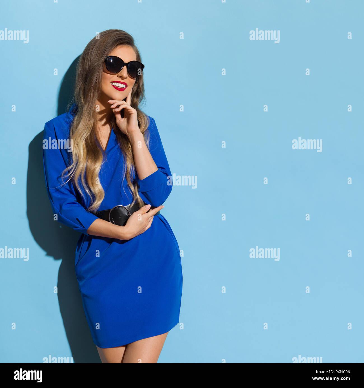 21229a83b9d2 Bella giovane donna in blu mini abito e occhiali da sole è in posa nella  luce