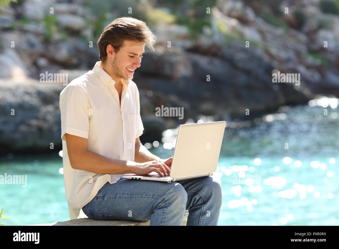Happy guy utilizza un laptop la scrittura dei messaggi di posta elettronica sulla vacanza estiva sulla spiaggia Immagini Stock