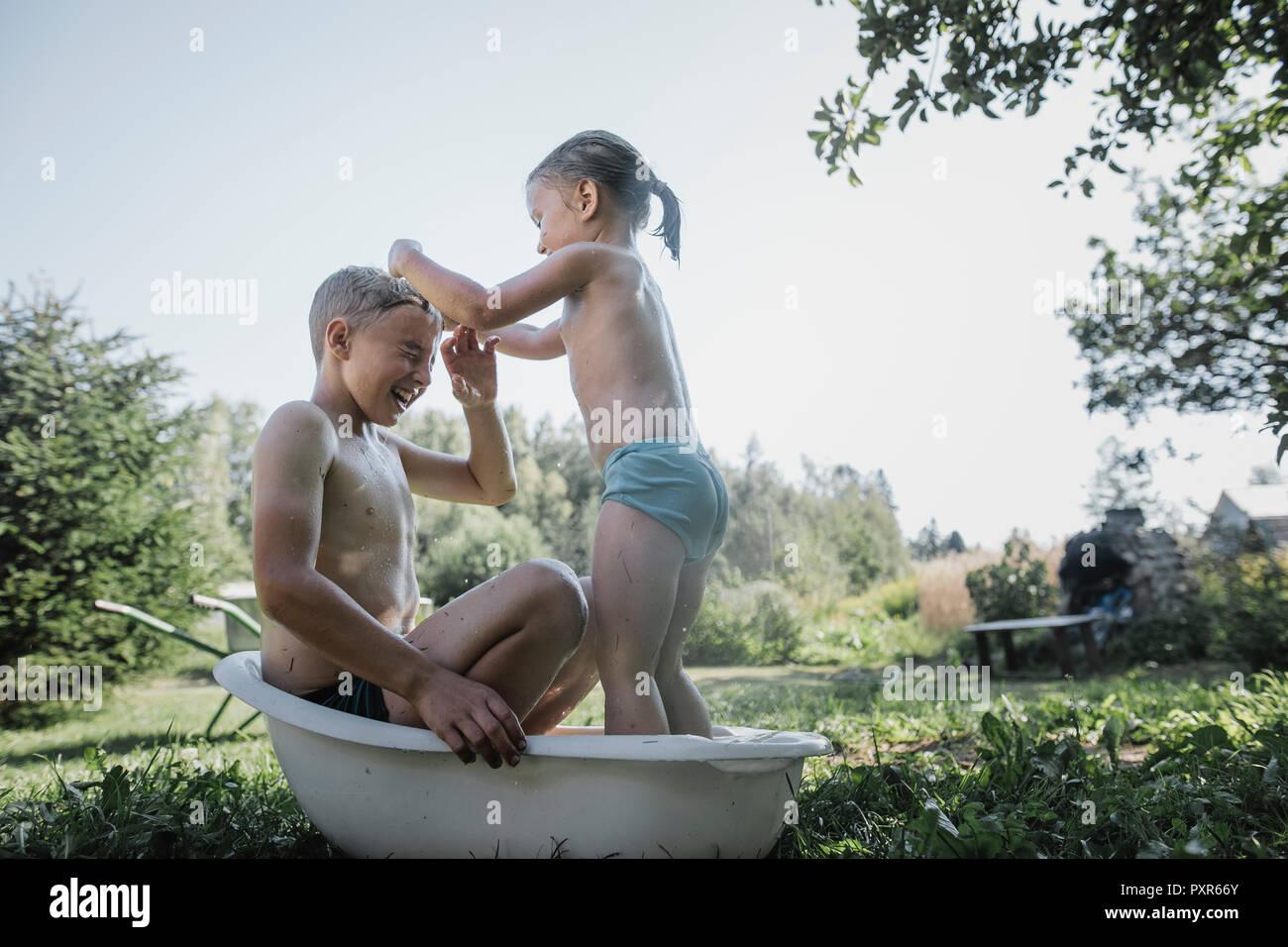 Fratello e sorella gioca con acqua nella piccola vasca da bagno in giardino foto immagine - Bambolotti che fanno il bagno ...