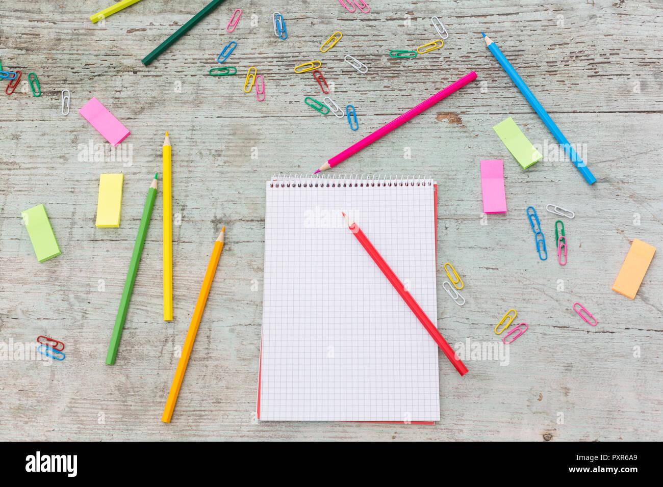 Notebook a spirale, fermaglio, marcatori e matite colorate su legno Foto Stock