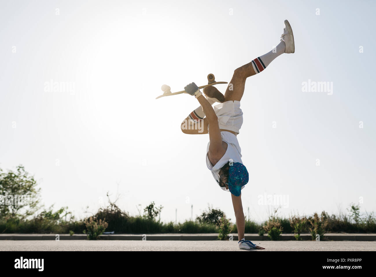 Vista laterale del uomo sportivo facendo eccitante trucco con skateboard flipping su un lato sulla strada Foto Stock