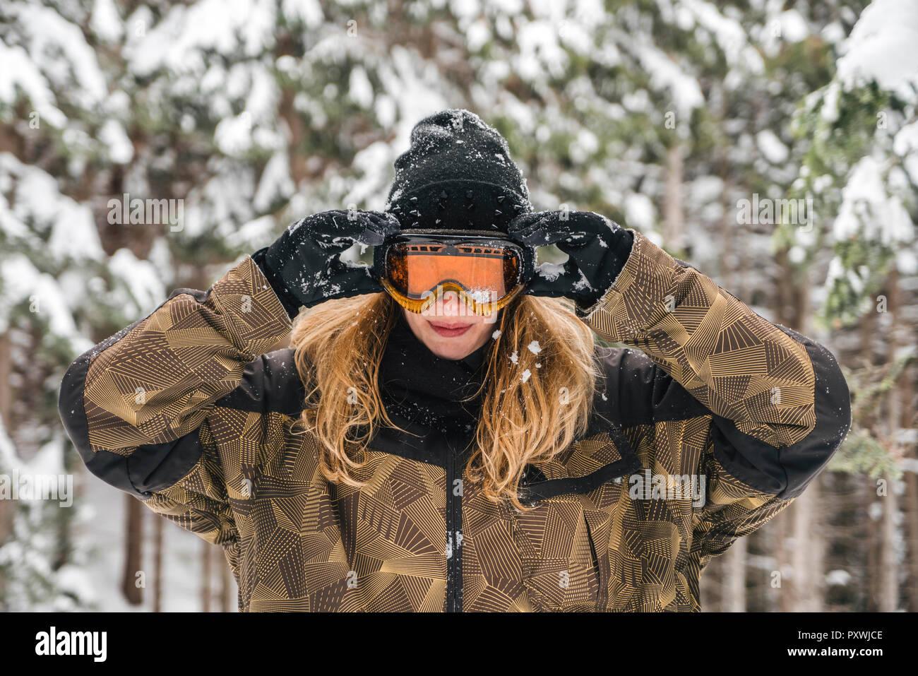 Giovane donna mettendo su occhiali da sci in inverno forest Immagini Stock