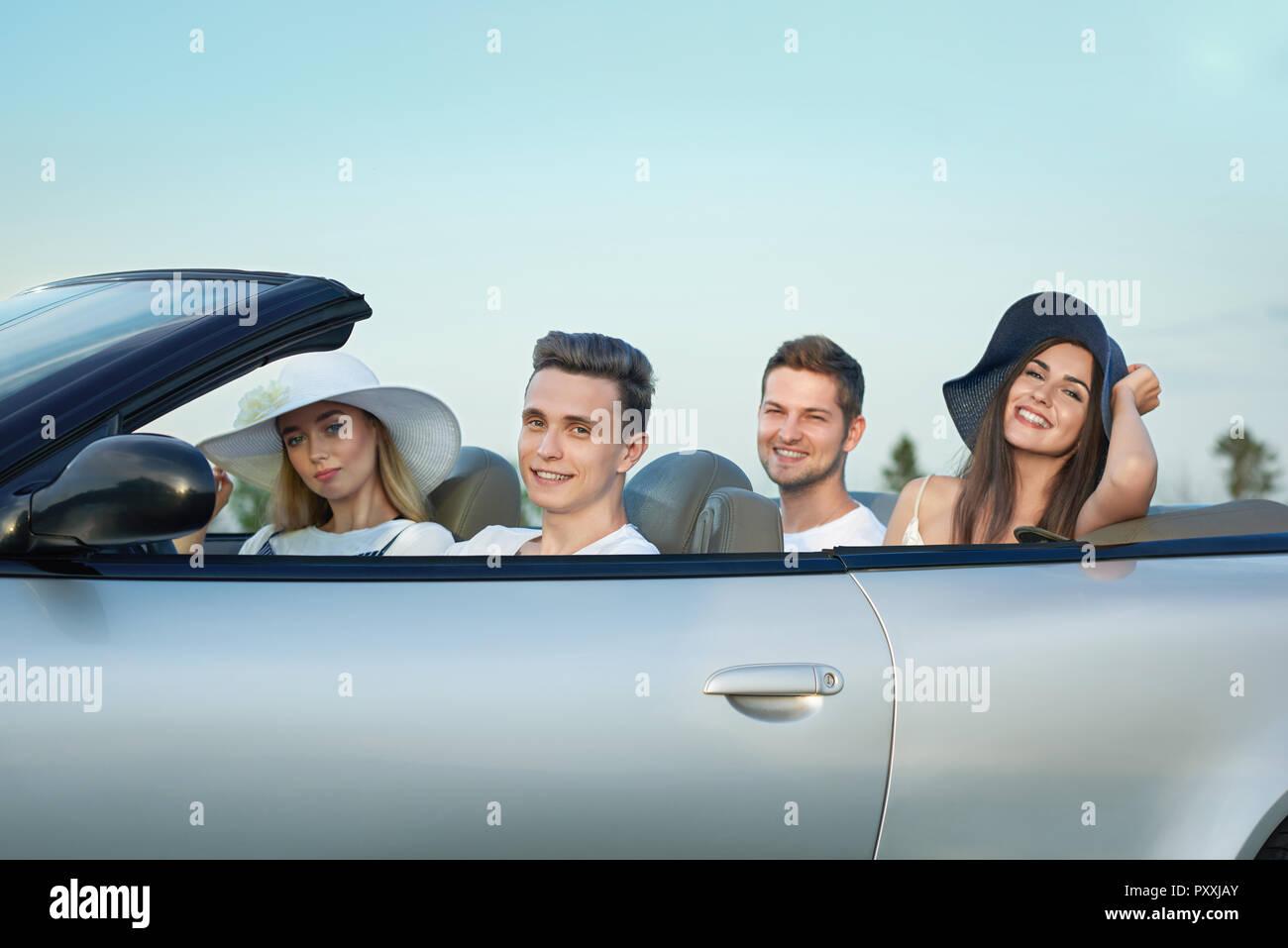 Il gruppo di quattro amici seduti in argento cabriolet e viaggiare in auto.  Piuttosto giovani 9354e9844974