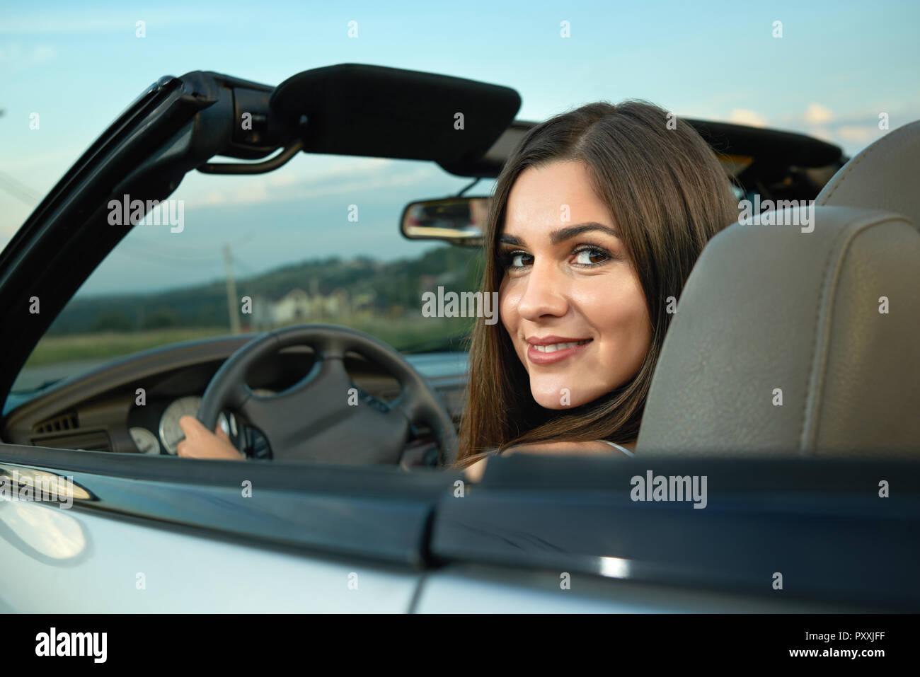Affascinante giovane donna alla guida di auto e guardando indietro alla  fotocamera. Splendido modello e 53a927aae9df