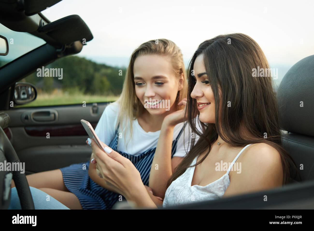 Bella bruna e biondo seduto sulla parte anteriore saet di automobile. Due  amiche in posa f5c7187317c9