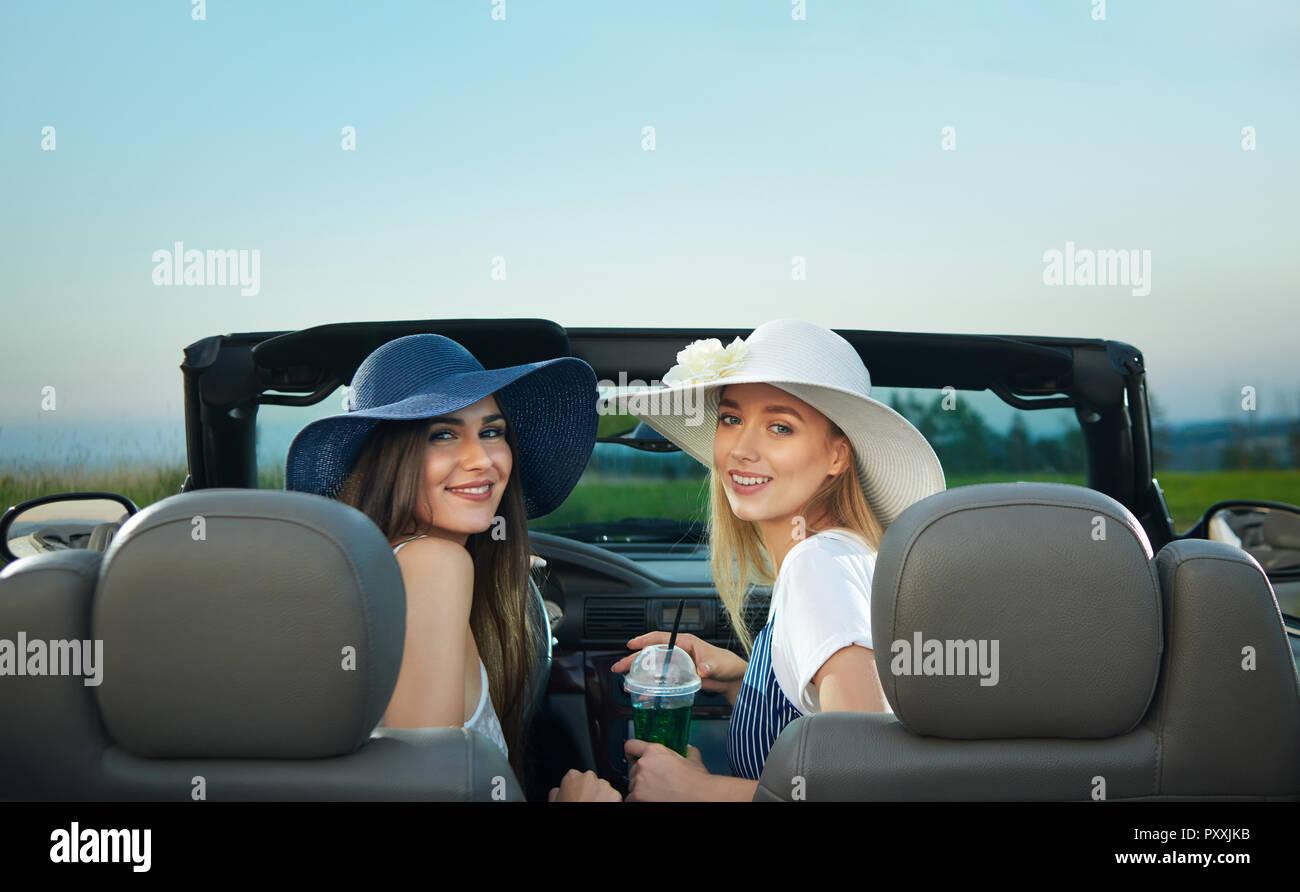Vista dal retro di due giovani donne seduti sui sedili anteriori del  cabriolet. Affascinante bruna e ... 5bbe84c3249a