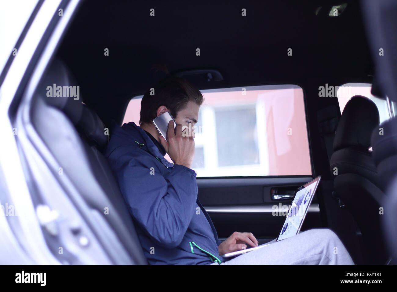 Business man utilizza un computer portatile e il telefono cellulare è seduto in macchina Immagini Stock