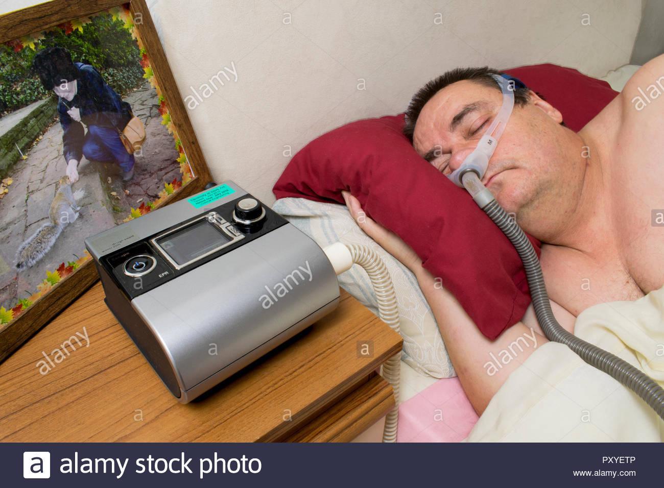 Uomo con CPAP Macchina e dormire maschera per il trattamento di apnea nel sonno Immagini Stock