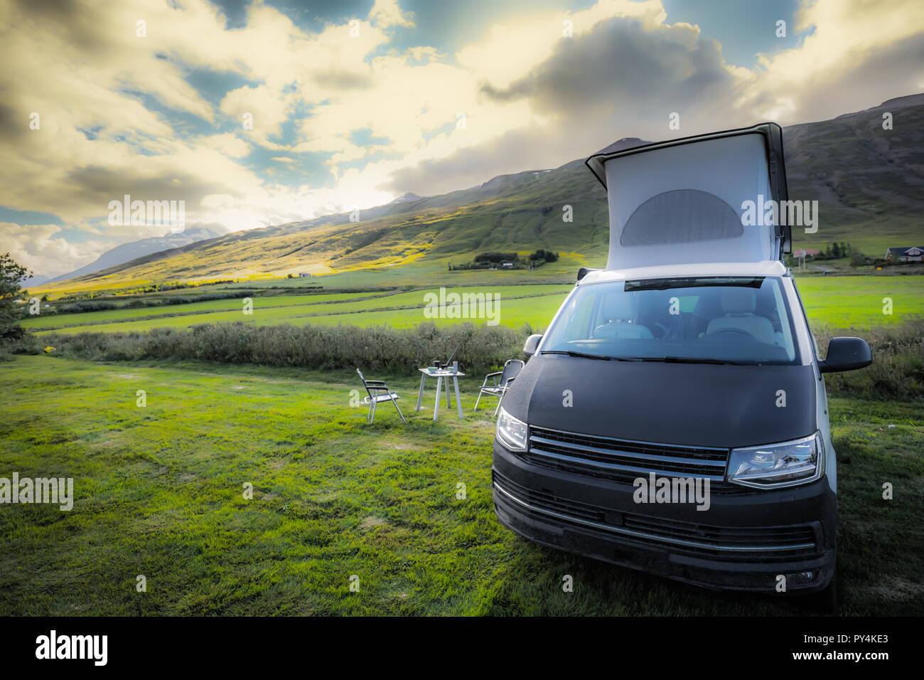 Camping bus nella luce solare con tetto aperto, tavolo e