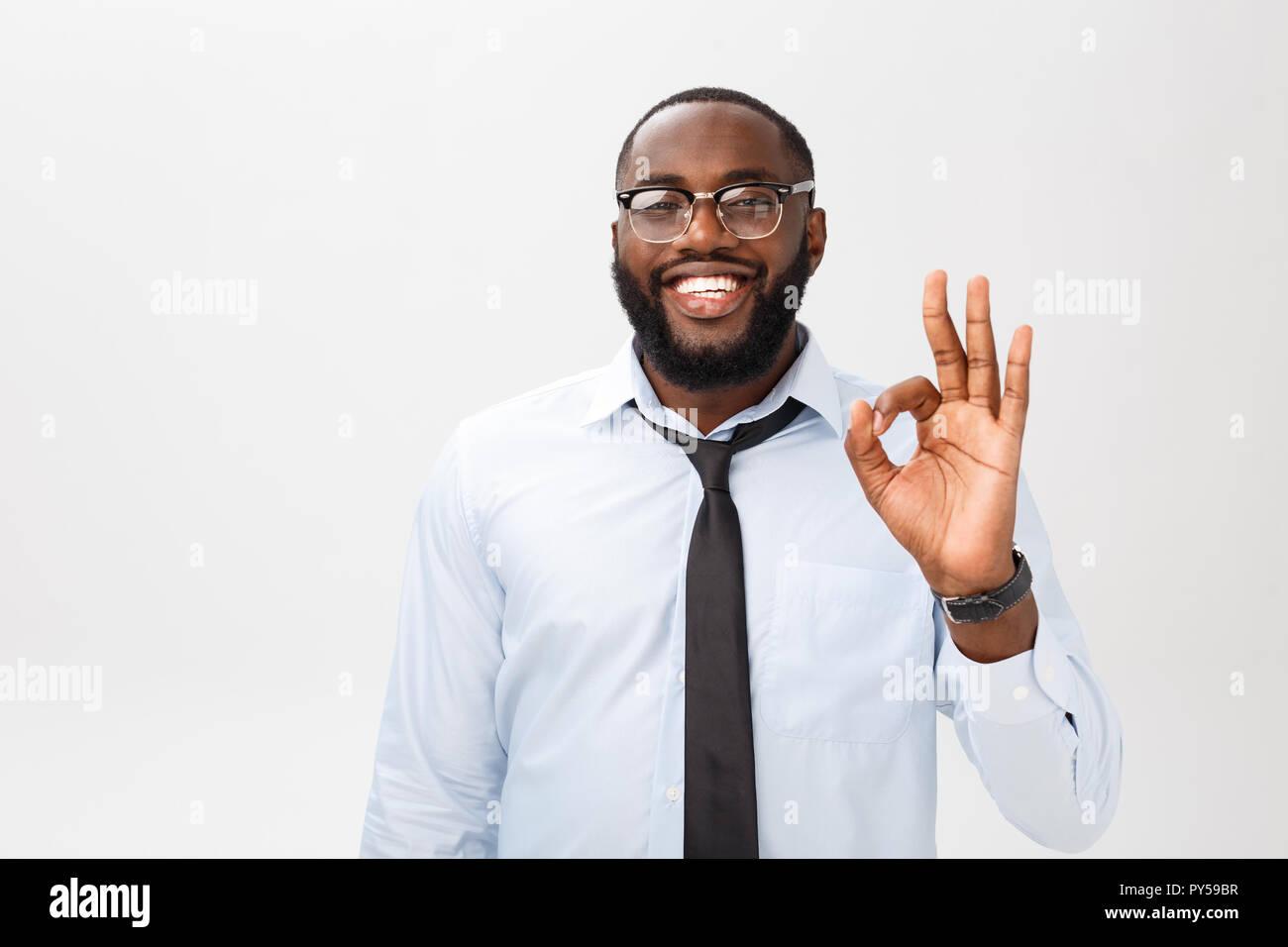 Ritratto di African American business uomo sorridente e mostrando buone condizioni di segno. Il linguaggio del corpo concetto Foto Stock