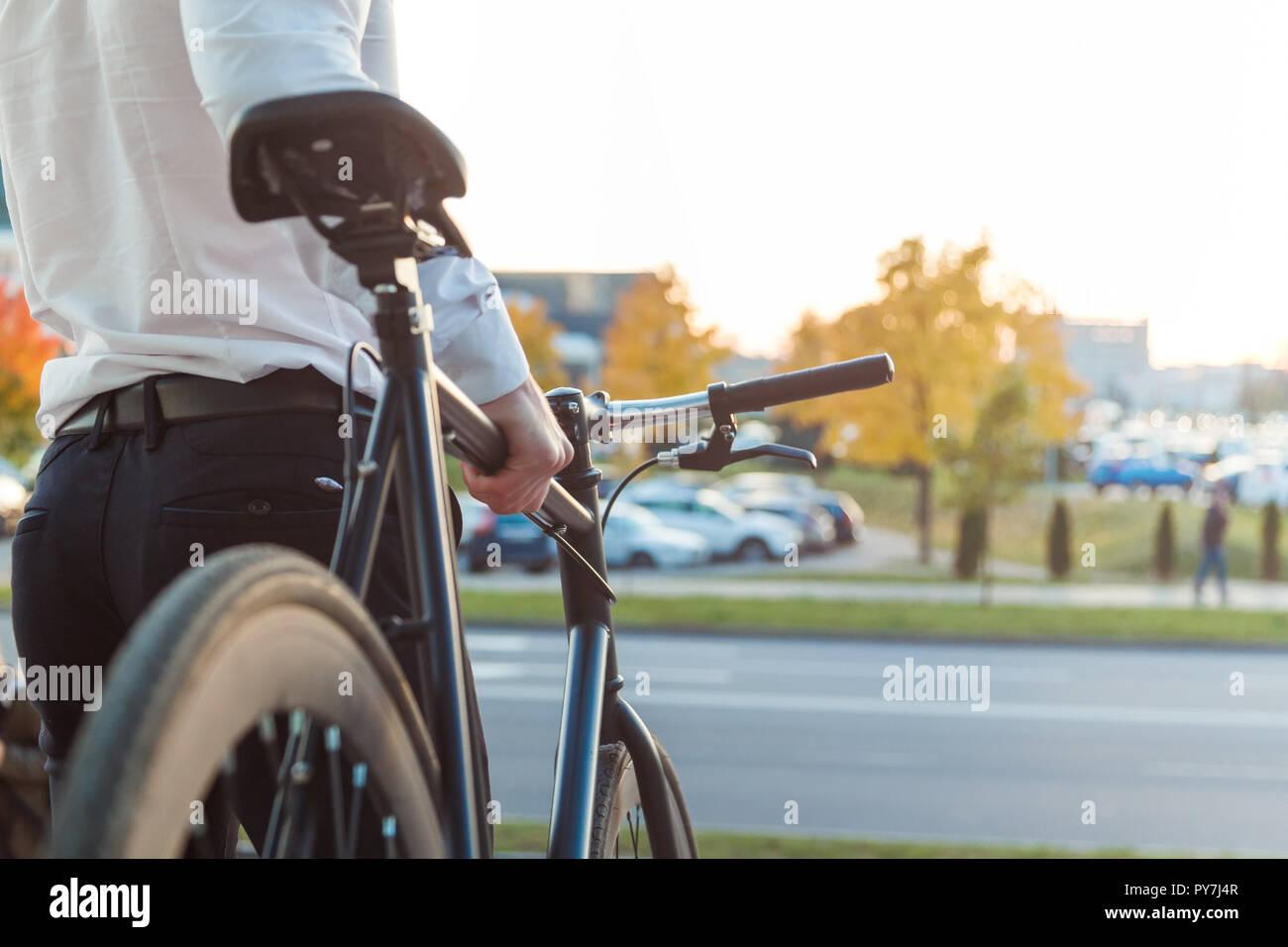 Imprenditore su una bicicletta. Uomo d'affari lasciando il suo lavoro. Dal retro. Foto Stock