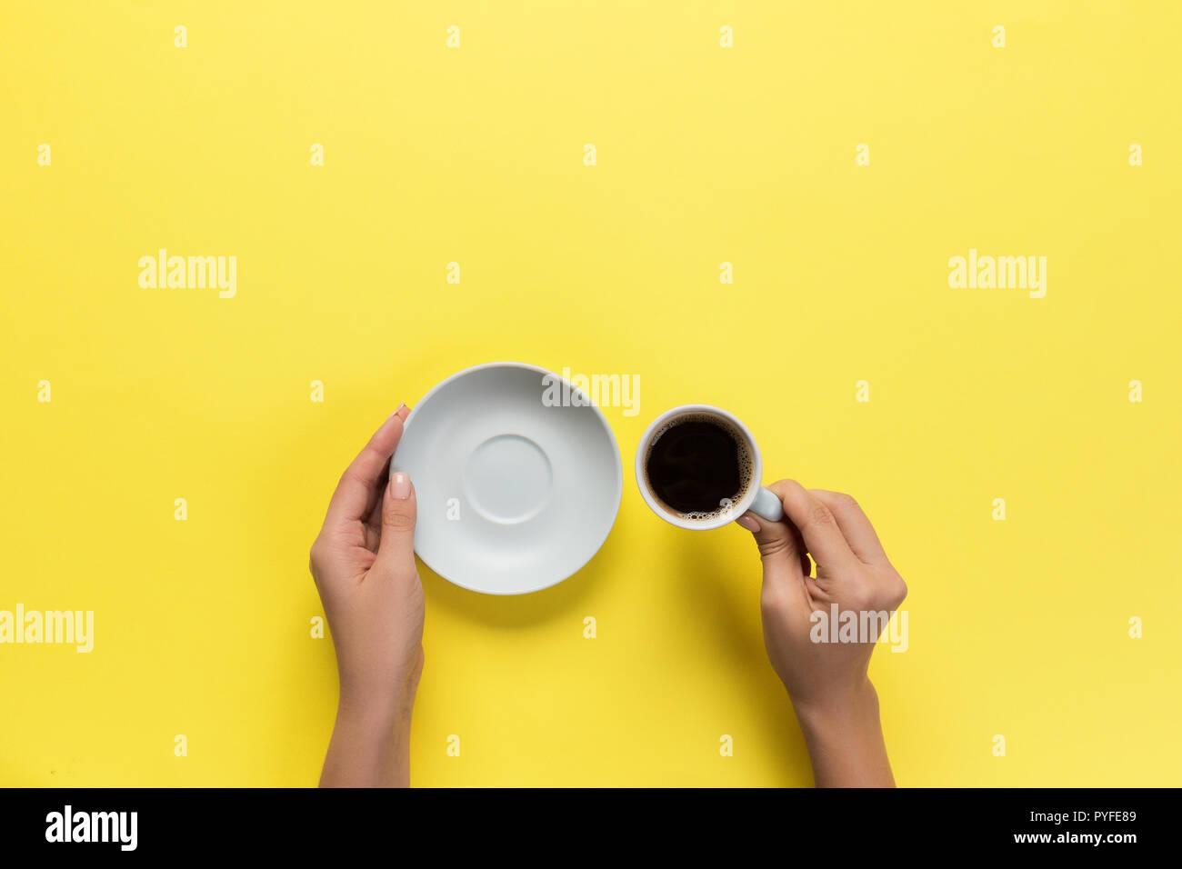 Elevato angolo di donna mani tazza da caffè su sfondo giallo stile minimalista. Appartamento laico, vista dall'alto isolato. Immagini Stock