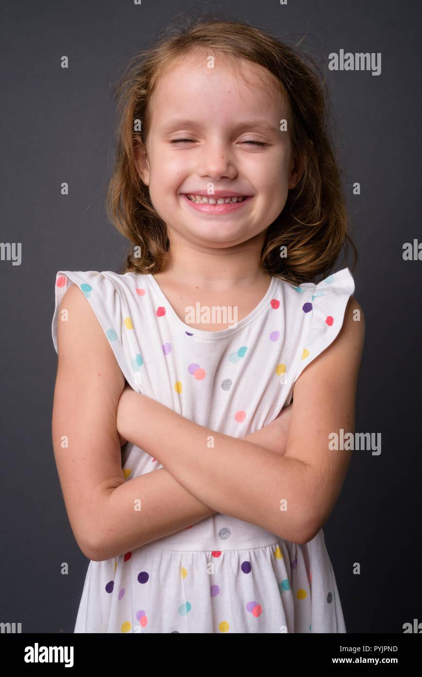 Carino ragazza giovane con capelli biondi contro uno sfondo grigio Immagini Stock
