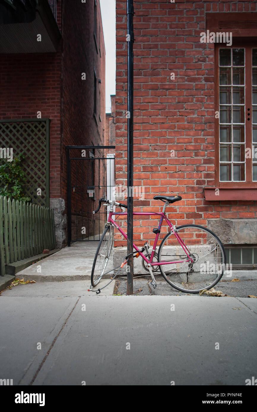 Un piatto rosso bike legato ad un palo bloccare entrambe le ruote e il telaio nella parte anteriore di un muro di mattoni in città. Vélo rouge devant onu Mur de brique. Immagini Stock