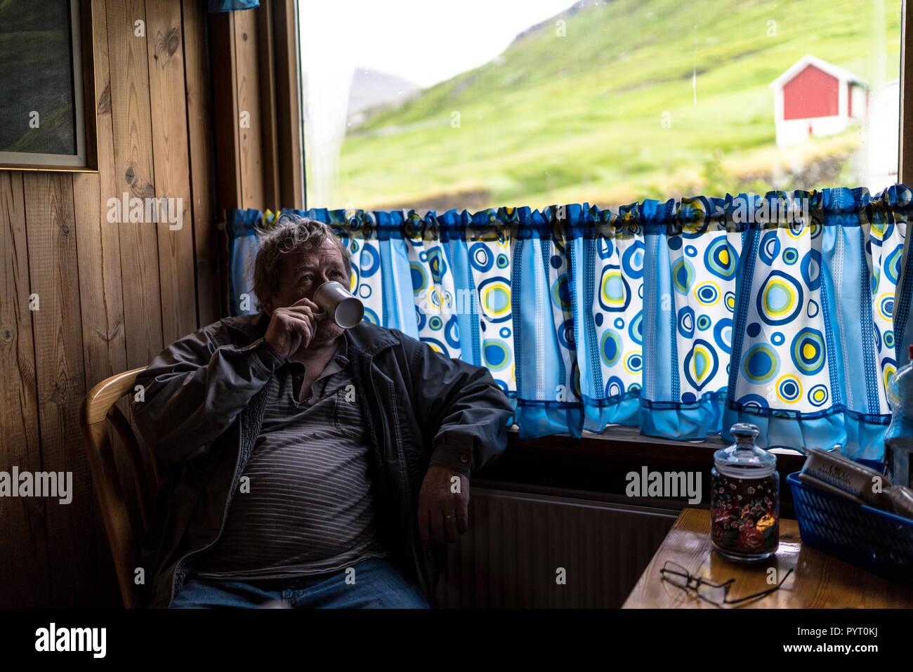 L uomo beve una tazza di the presso la casa, Funningur, Eysturoy isola, isole Faerøer, Danimarca Immagini Stock