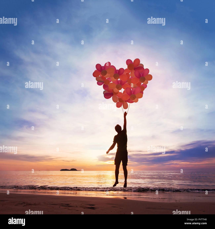 La gentilezza e il concetto di amore, bambino battenti con cuore da palloncini. Immagini Stock