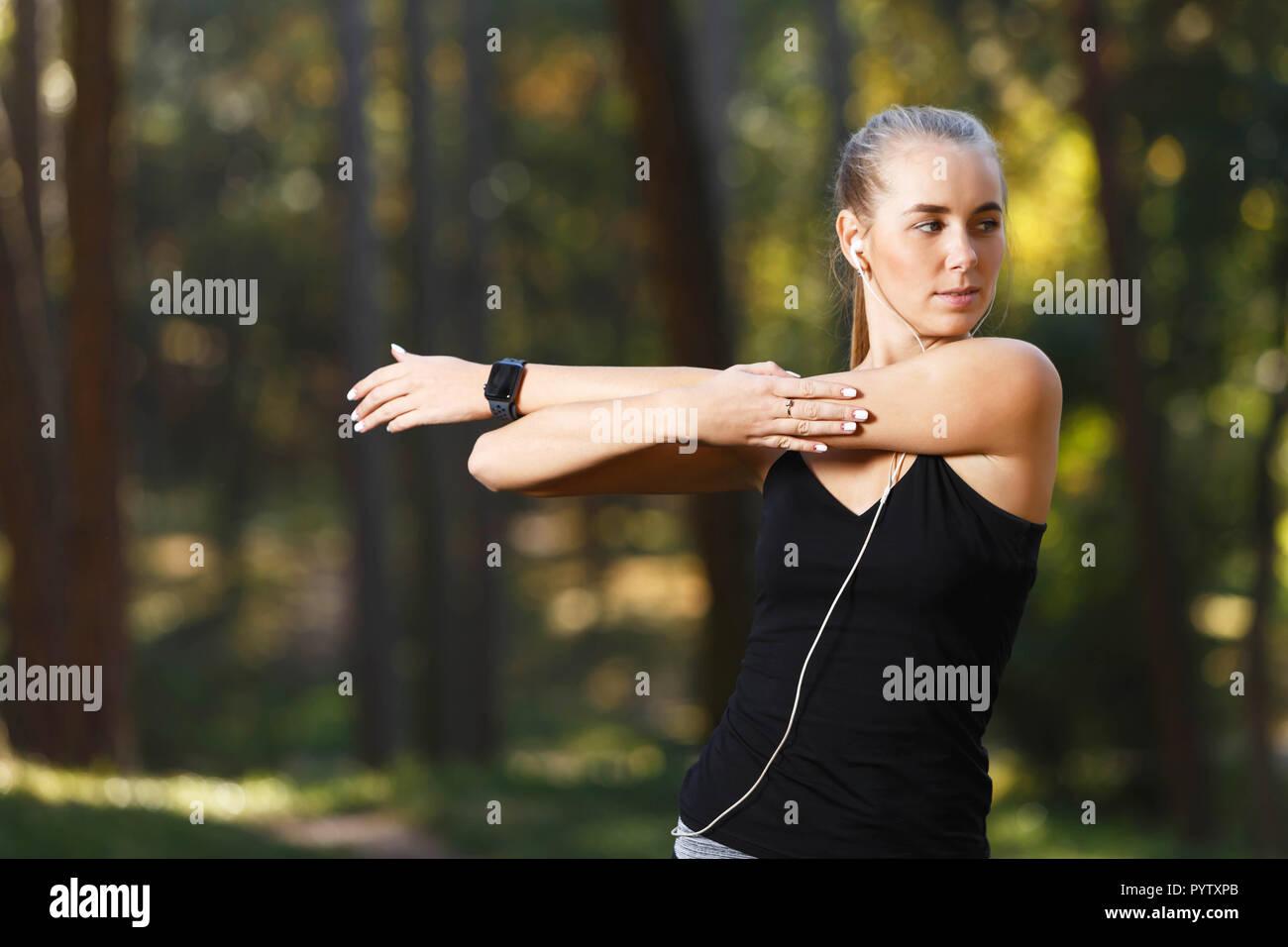 Ritratto di giovane donna atletica indossando vestiti sportish stretching e ascolto di musica nel soleggiato parco, uno stile di vita sano e concetto di persone Foto Stock