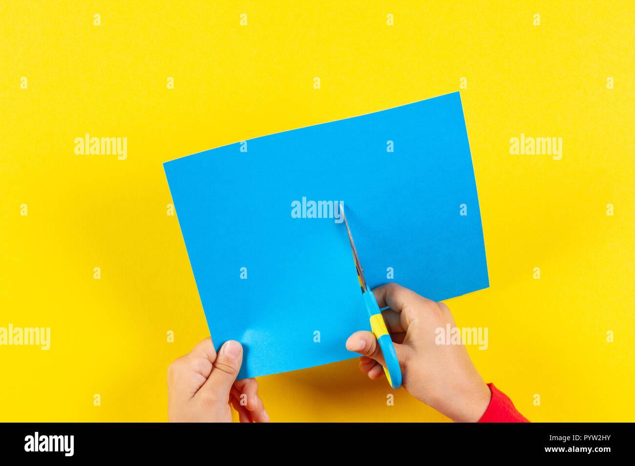 Il capretto con le mani in mano il taglio di carta colorata con le forbici. Immagini Stock