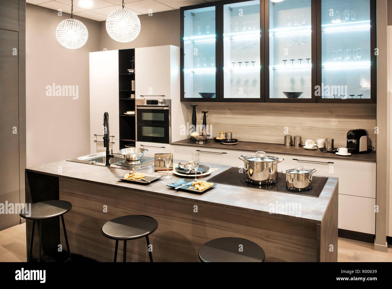 Marrone neutro una cucina moderna con interni isola con built-in piano di cottura e lavandino e sgabelli bar illuminata da grandi finestre lungo una parete Immagini Stock