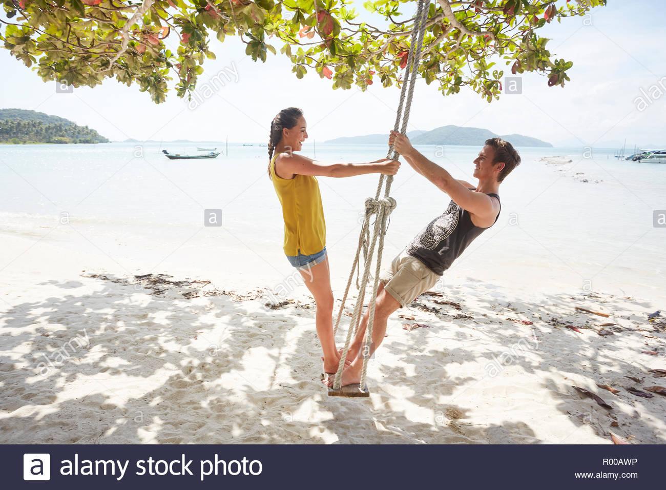 Coppia giovane sulla spiaggia swing Immagini Stock