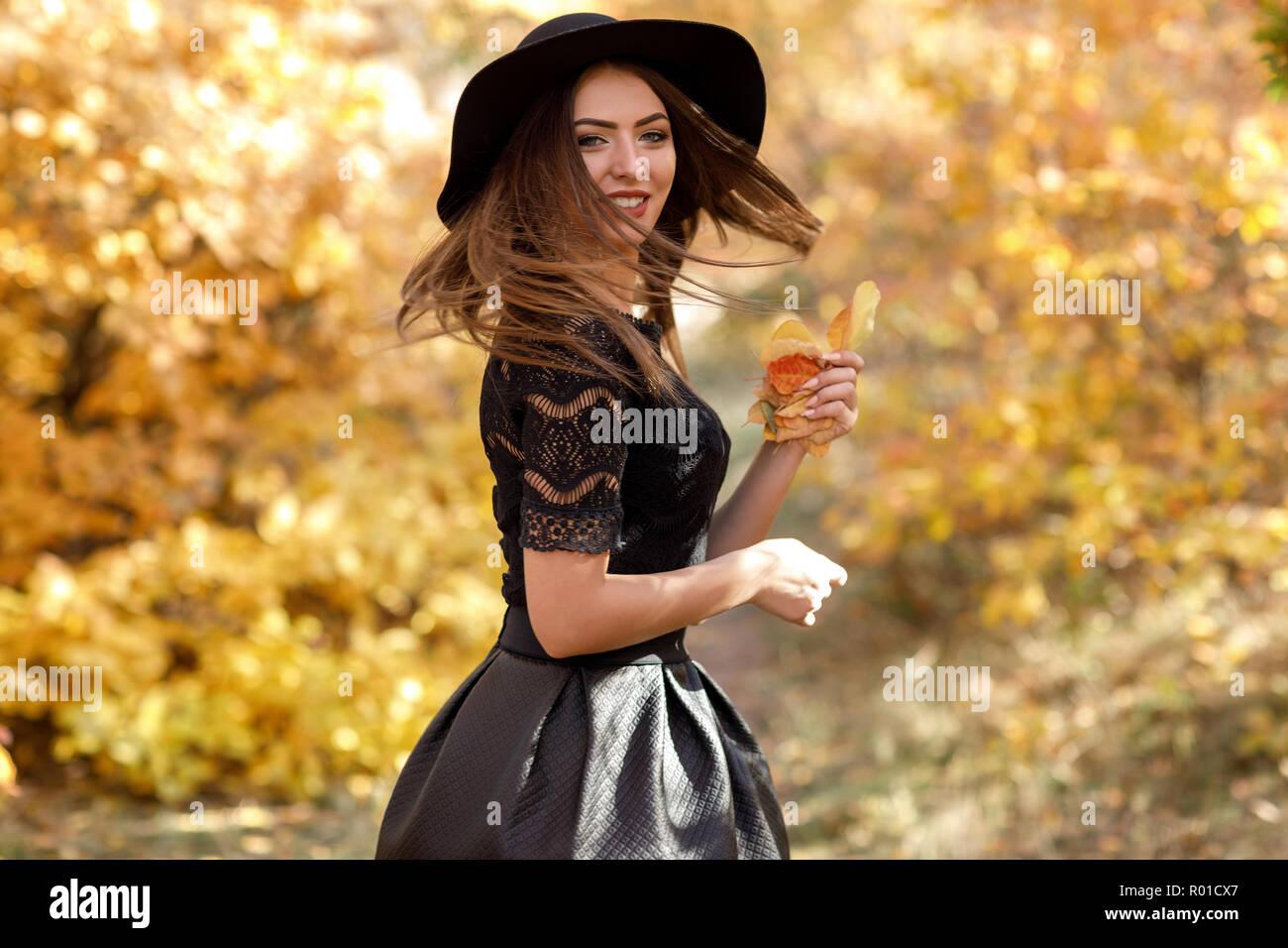 82f4df7ec280 Bella donna in abito nero e il cappello in autunno Foto   Immagine ...