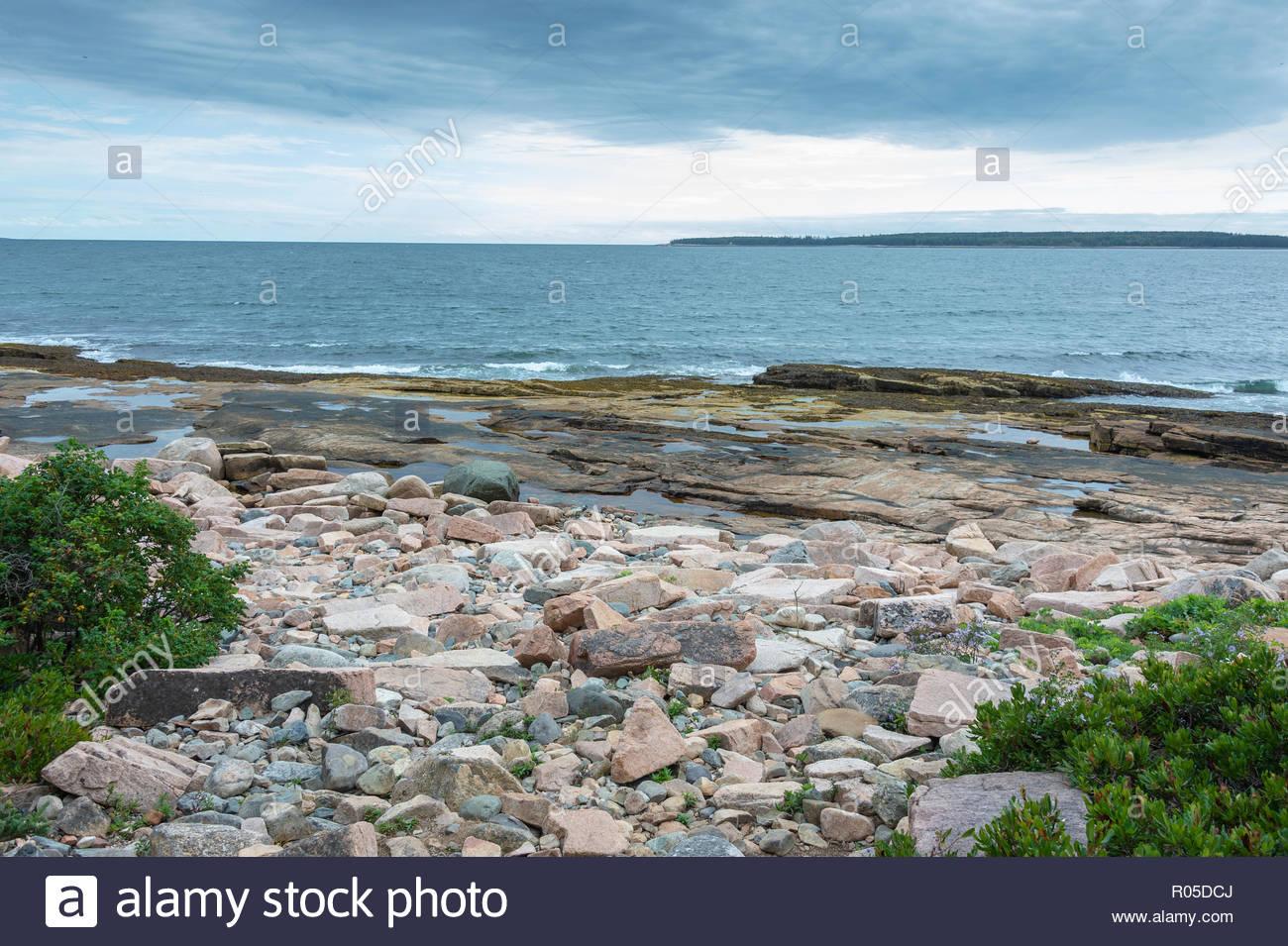 Sentiero delle meraviglie della costa di Granito frantumato e pozze di marea con grande Gott isola in background Immagini Stock