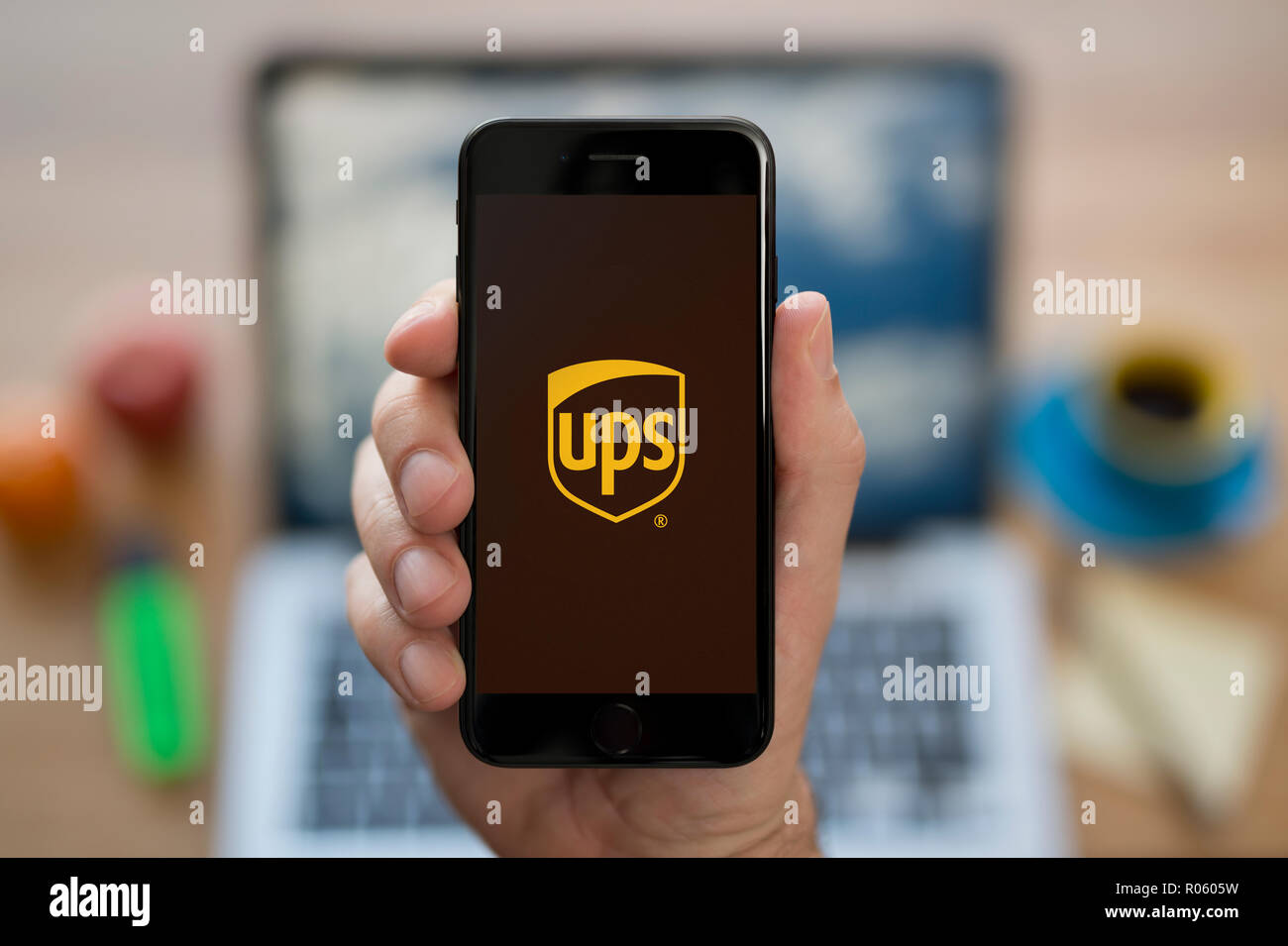 Un uomo guarda al suo iPhone che visualizza il logo UPS, mentre se ne sta seduto alla sua scrivania per computer (solo uso editoriale). Immagini Stock