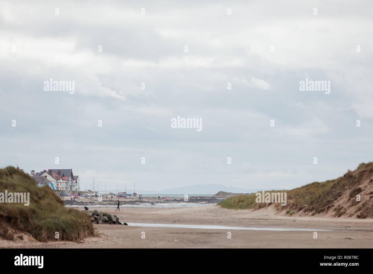 Vista di Rhosneigr da attraverso le dune di sabbia sulla spiaggia Cymyran, Anglesey, Galles del Nord, Regno Unito Foto Stock