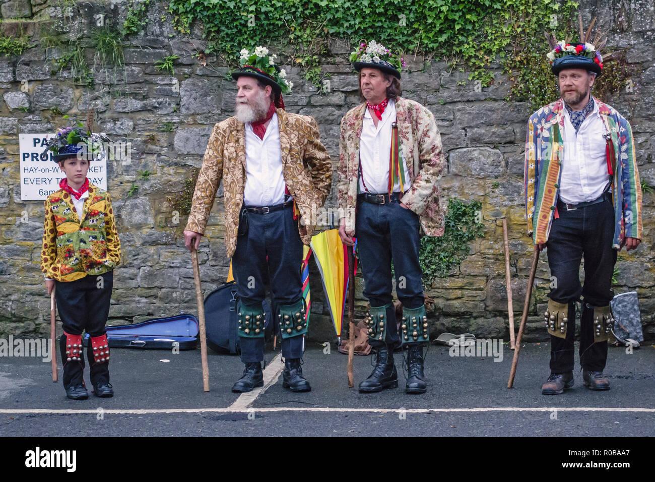 Hay-on-Wye, Powys, Wales, Regno Unito. Morris ballerini (3 uomini e un ragazzo) in costume tradizionale in attesa di danza nella piazza della città Immagini Stock