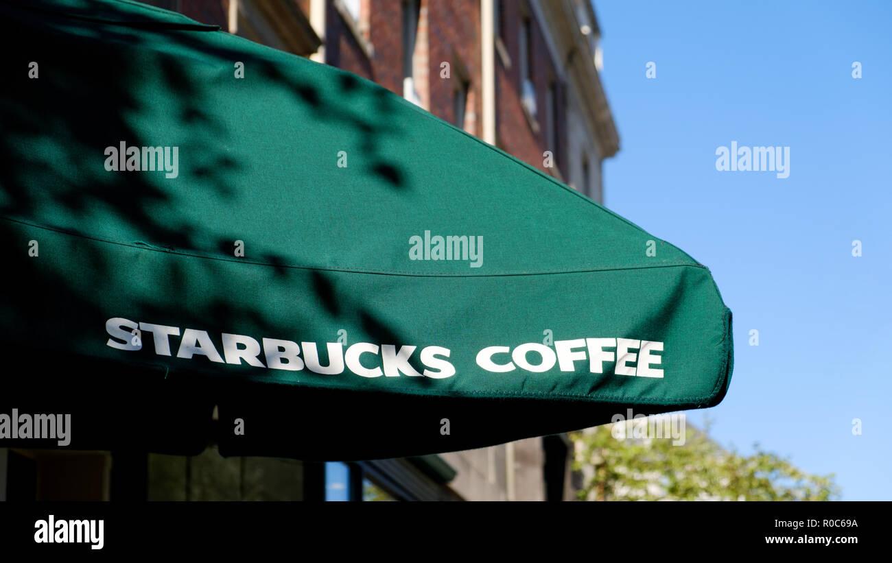 Un Starbucks Coffee shop ombrello aperto che mostra chiaramente il marchio Stabucks nome e colori del marchio su un luminoso giorno di sole Immagini Stock