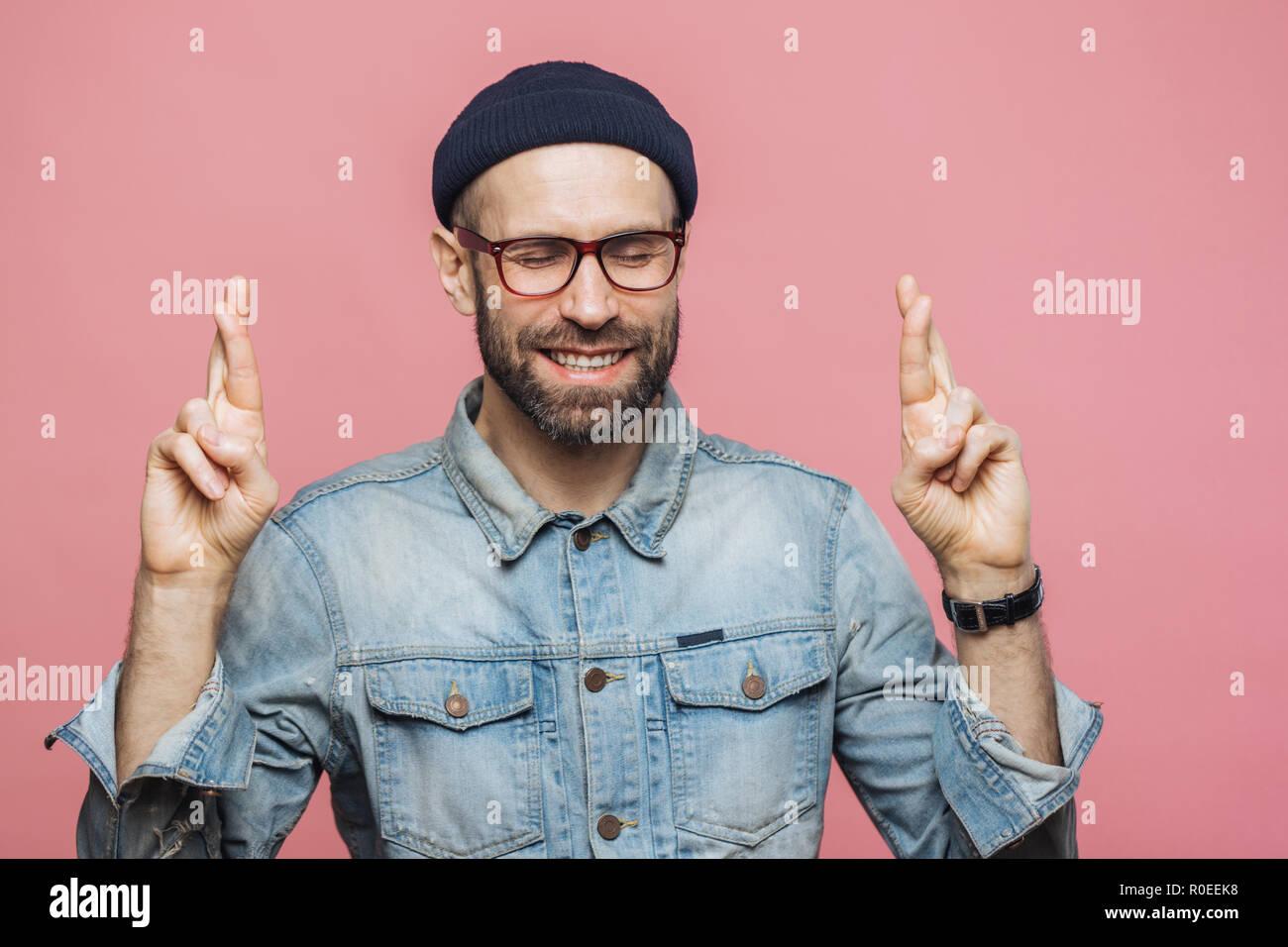 Piscina colpo di bello barba lunga maschio mantiene le dita incrociate, chiudere gli occhi, è felice espressione, vestito in abiti alla moda isolato su rosa backg Immagini Stock