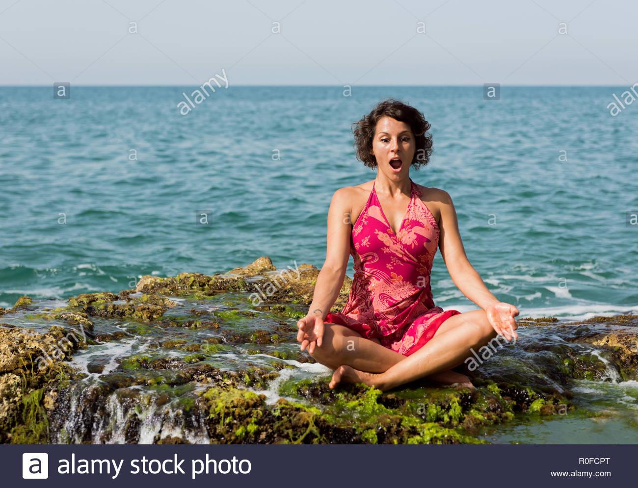 f3e09944f8fd Giovane donna in abito modellato esegue Lotus pongono su una roccia vicino  al mare con faccia