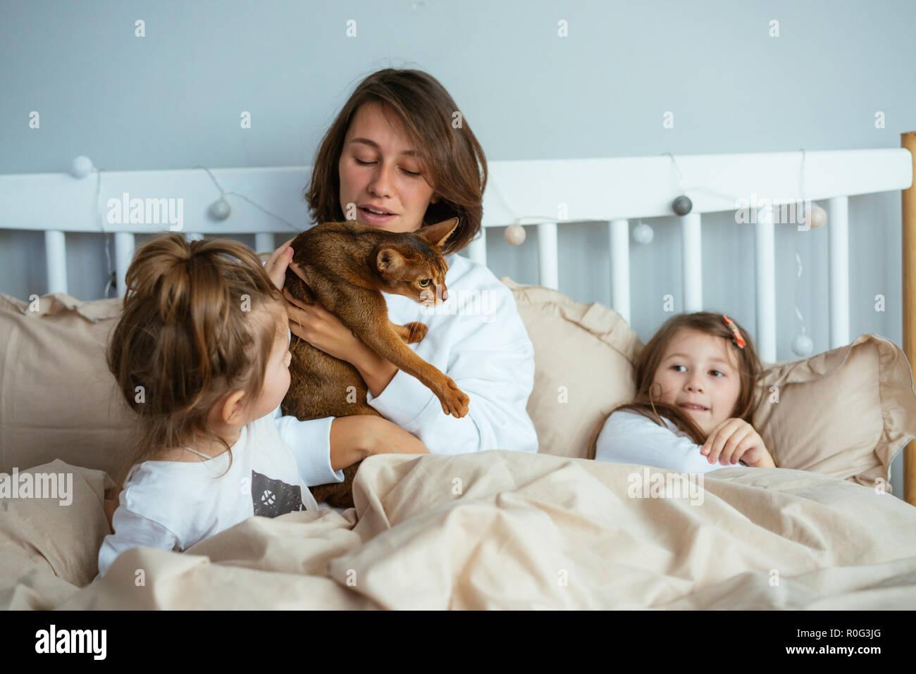 Felice e madre di due figlie sorridente abbracci a letto Foto ...